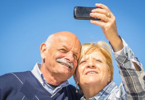 jubilados felices tomándose una selfie con un celular