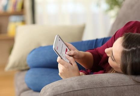 Mujer en el sofá solicitando un préstamo rápido y online por el celular